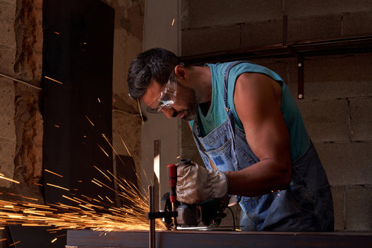 Side view of workman in protective glasses and gloves cutting metal with grinder with flying sparks while working in workshop