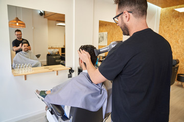 Stock vertical photo of barber drying hair with a hairdryer to a client in front of a mirror. Barbershop