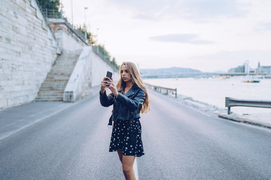 Long haired stylish woman taking selfie with smartphone