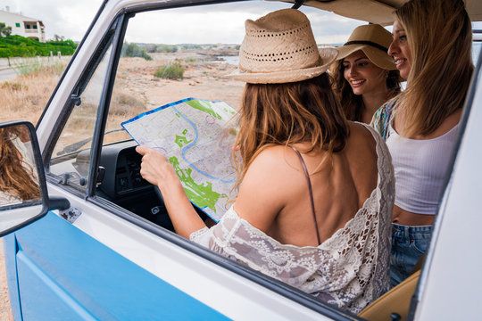 From above group of touristic charming ladies in hat with open back studying map for navigation in trip in blue car