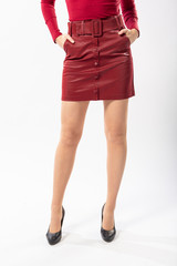 a girl with beautiful slender legs in a short red leather skirt on a white background, a girl in a red leather short skirt and a red jacket on a white background