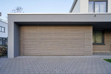 A modern Scandinavian-style garage with a wood-paneled garage door. Private garage with automatic door in a European city in Germany