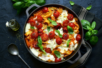 Pasta casserole with tomatoes and mozzarella cheese in a cast iron pan. Top view with copy space.