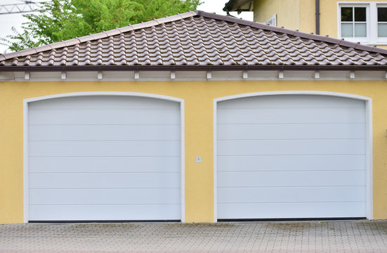 Two white garage doors in a European city. Garages for two cars