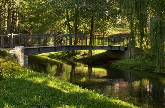 Footbridge over Lyna river and alley Chateauroux at Park Podzamcze in Olsztyn. Poland