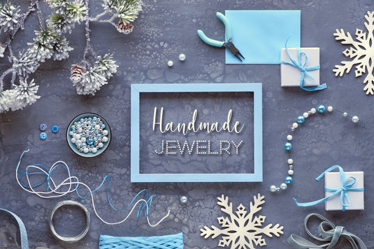 """Making handmade jewelry for friends as Winter holiday gifts. Creative diy craft hobby. Flat lay on dark textured background, text """"Handmade jewelry""""."""