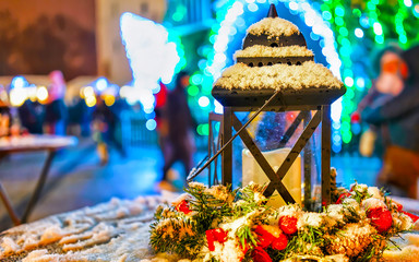 Street lamp with candles at Christmas Market at Vilnius in Winter Lithuania. Light lantern Advent Fair Decoration and Stalls with Crafts Items on Bazaar. Lithuanian street Xmas and holiday