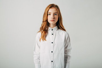 A young red-haired girl is looking at the camera. A student with red hair suffers from bullying. Isolate on a white background.