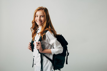 A young red-haired girl goes to school. Schoolgirl looking over her shoulder and goes to study lessons. Isolate on white background