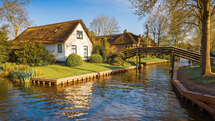 Lovely landscape with canal, wooden footbridges and Dutch houses at sunset,  Giethoorn, Netherlands