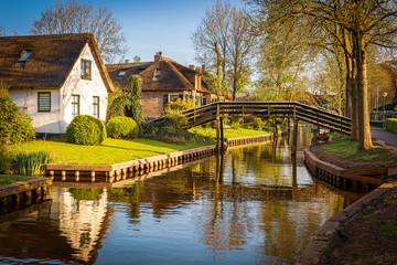 Lovely landscape along canal with footbridges and beautiful thatched cottages, Giethoorn, Netherlands