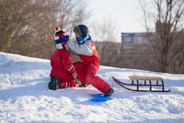 Older brother takes care of his younger brother on a snow hill