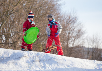 Two boys at the sledge on the top of snowy hill waiting for ridi
