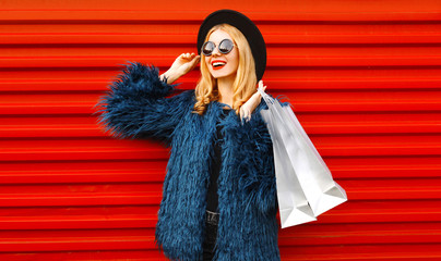 Portrait stylish smiling woman with shopping bags wearing blue faux fur coat, round hat and...