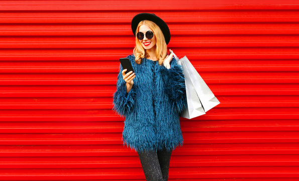 Stylish smiling woman with phone and shopping bags wearing blue faux fur coat, round hat and sunglasses over red wall background