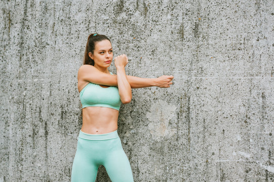 Outdoor portrait of young beautiful fit woman stretching arms, wearing green activewear, athlete model posing next to grey urban wall background, sport fashion