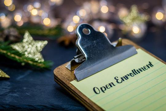 Open Enrollment healthcare choices still life concept on clipboard on dark slate and winter decor