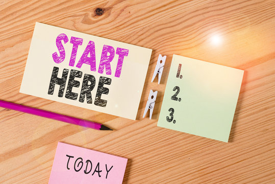 Conceptual hand writing showing Start Here. Concept meaning telling someone this is beginning point to go from to destination Colored crumpled papers wooden floor background clothespin