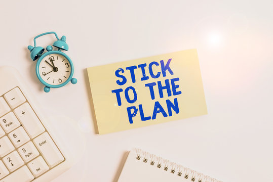 Conceptual hand writing showing Stick To The Plan. Concept meaning To adhere to some plan and not deviate from it Follow Keyboard with empty note paper and pencil white background