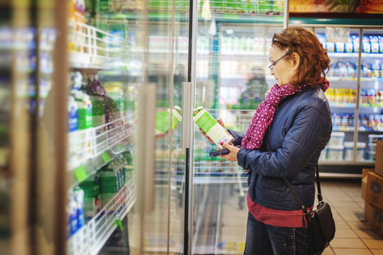 Mature woman 60 years old pensioner chooses a pack of milk from a shelf in a grocery supermarket, reads the label