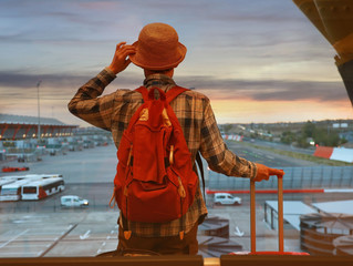 Back view of young  backpacker man  and a luggage which looking the airplane on the window  at a terminal airport