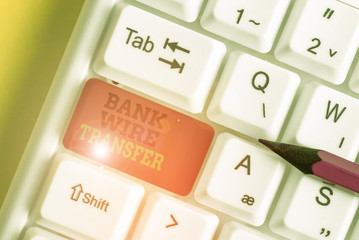 Handwriting text writing Bank Wire Transfer. Conceptual photo Electronic transfer of money through bank to bank White pc keyboard with empty note paper above white background key copy space