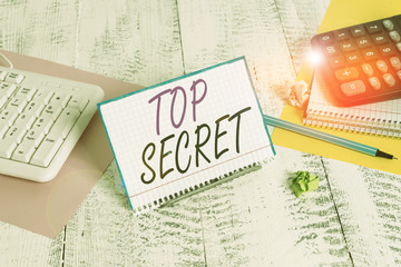 Text sign showing Top Secret. Business photo text protected by a high degree of secrecy Highly confidential Notepaper stand on buffer wire in between computer keyboard and math sheets