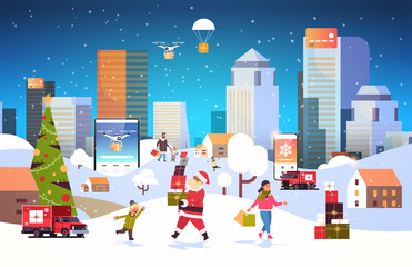 santa claus carrying gift boxes people with shopping bags walking outdoor preparing for christmas new year holidays men women using online mobile application winter cityscape background horizontal