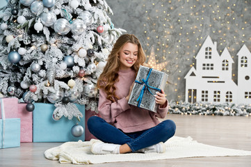 Beautiful girl in pink sweater with christmas box gift near pink and blue Christmas tree. Magical...