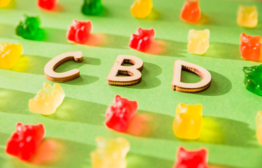 Wooden letters CBD on a green background and gelatin in the form of bears. View from above. The shadow of the sun falls on the background