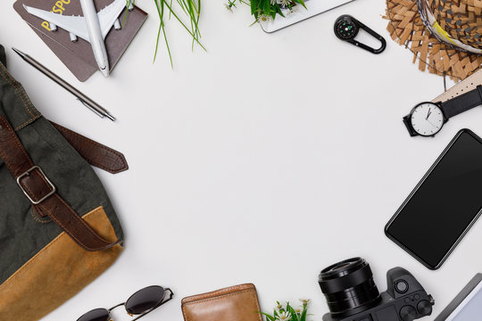 Top view mockup of Traveler's accessories with passport, books of travel plan, wallet, camera, hat, backpack and airplane toy isolated white background with empty space,Tropical travel concept