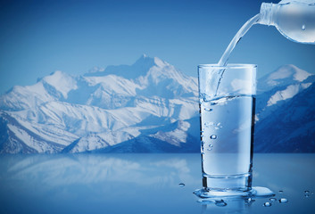Pouring mineral water from bottle into a glass with water drops in the iceberg background,...