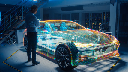 In Automotive Innovation Facility Automobile Design Engineer Working on 3D Holographic Model Projection of Electric Car. Futuristic Concept of Virtual and Augmented Realty Use.