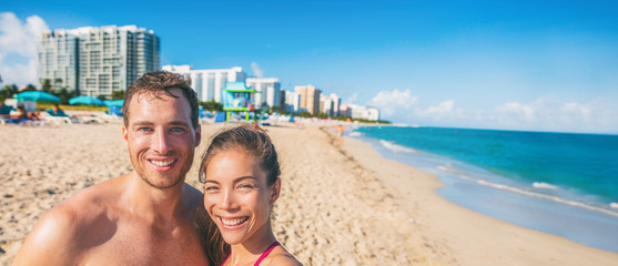 Miami beach happy couple taking selfie on USA Florida on summer travel winter vacation. Interracial people smiling on south beach. Biracial Asian girl, young man banner panorama.