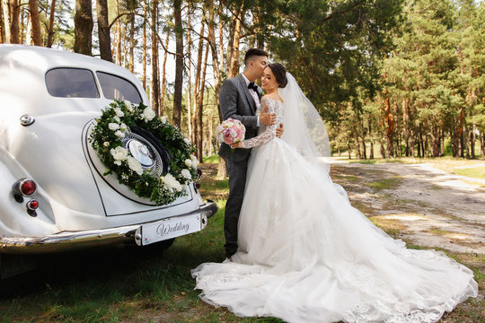 """Luxury wedding photography. Elegant wedding couple, groom in grey suit and bride in wedding dress with long sleeves and long train kissing near white Just Married car with inscription """"Wedding"""""""
