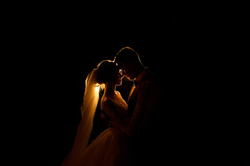 Creative idea of wedding photography at night. Silhouette of a bride and groom illuminated by a lights