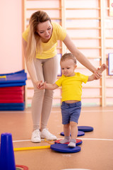 little toddler doing steps on fitness plate with mom's help in the gym class