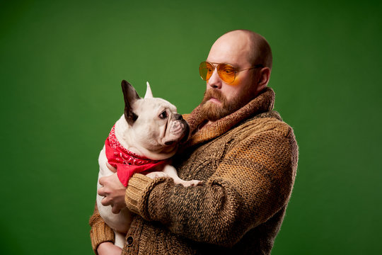 Man in glasses with french bulldog in in red bandana his arms