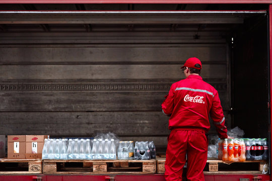 Minsk, Belarus - Nov 2018. Lorry with boxes of Coca-cola, water and juice. Delivery worker checks an order. Food and drink delivery to restaurant, pub, cafe
