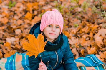 Little girl in a blue jacket and pink knitted hat holds a leaf and sits on blanket in the autumn's park. Leaves. Childhood. Fall. Leisure. Yellow. Orange
