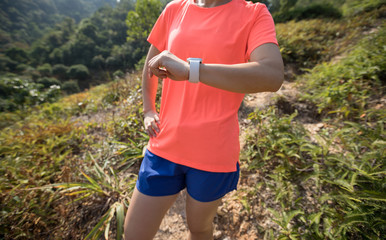 Woman trail runner looking at her smartwatch before running at tropical forest mountain trail