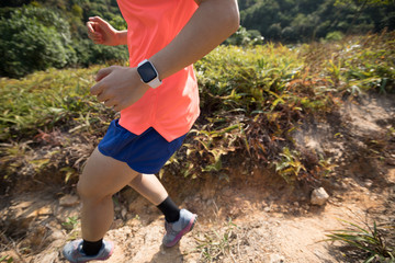 Woman trail runner running downhill on mountain slope in tropical forest