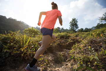 Woman ultramarathon runner running up on mountain slope in tropical forest