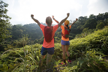 Two women trail runners open arms to surnise after running to the top of tropical forest moutain