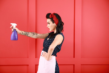 Portrait of beautiful tattooed pin-up housewife with detergent on color background