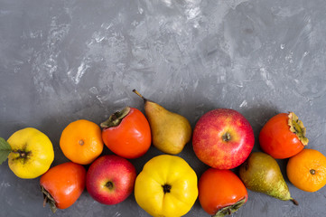 Different seasonal fruits on a concrete background. Source of vitamins and health. Healthy eating concept. Copy space.