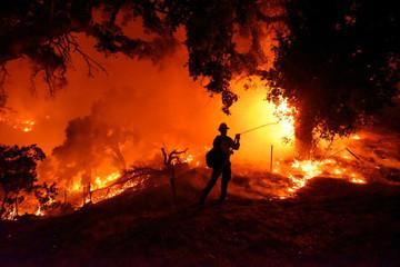 Santa Barbara City firefighter Erik Adair battles flames near a home off Cieneguitas Rd in Santa Barbara, California