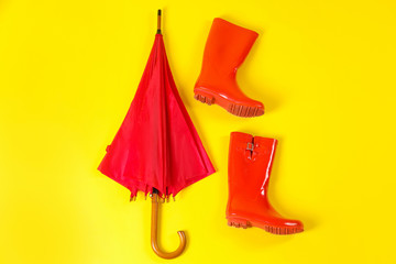Wall Mural - Beautiful red umbrella and rubber boots on light yellow background, flat lay