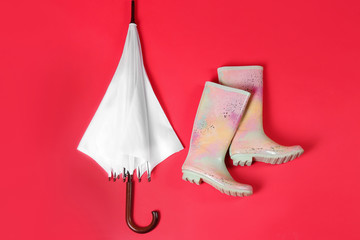 Wall Mural - Beautiful white umbrella and colorful rubber boots on red background, flat lay