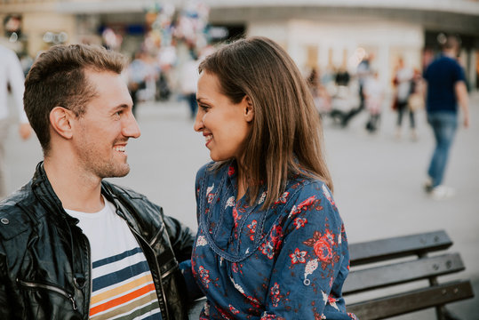 Closeup of young loving couple looking at each other while sitting on a bench